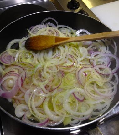 En una sartén, a fuego medio/bajo, calienta un poco el aceite y agrega las semillas de comino y pimienta, después incorpora las cebollas y un poco de sal.